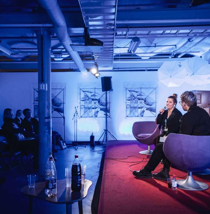 Kaksi henkilöä lava haastattelussa ja yleisöä/ Two people on stage interview and some audience