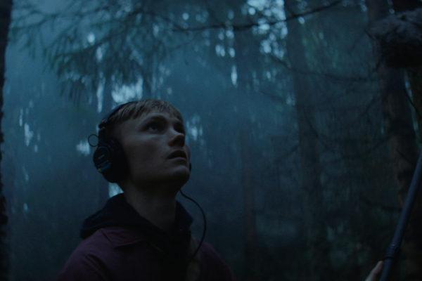 Mies seisoo pimeässä metsässä / Man standing in a dark woods