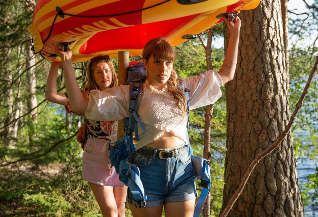 Kaksi tyttöä kantaa kumivenettä / Two girls carrying an inflatable boat
