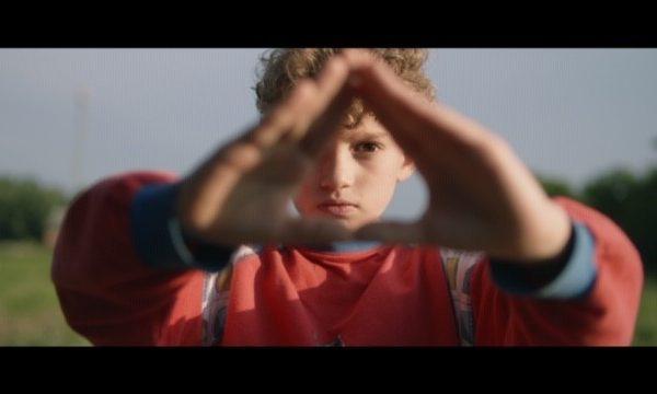 Poika katsoo kameraan käsien takaa / Boy