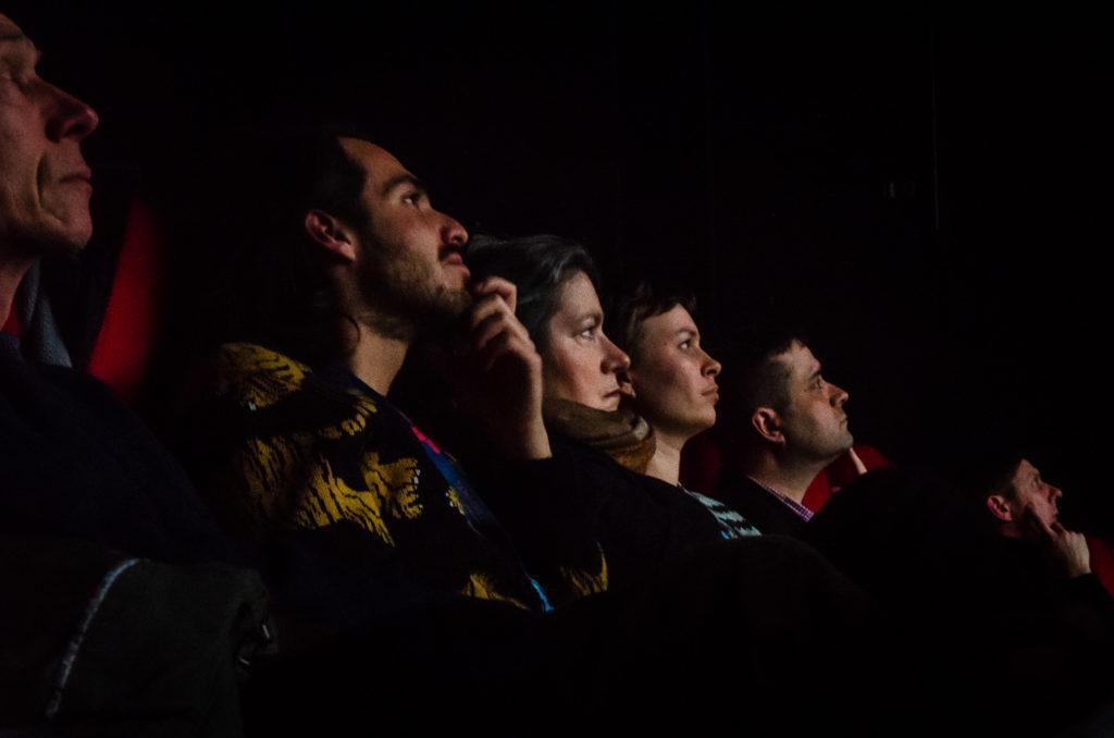 Ihmisiä istumassa yleisössä / People sitting in the audience