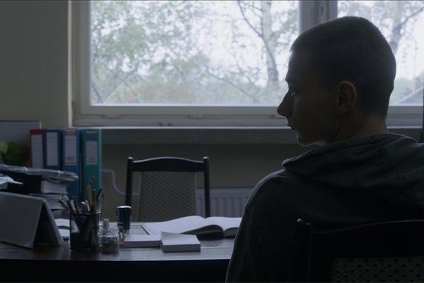 Poika istumassa toimistossa