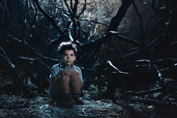 Poika istuu pimeässä