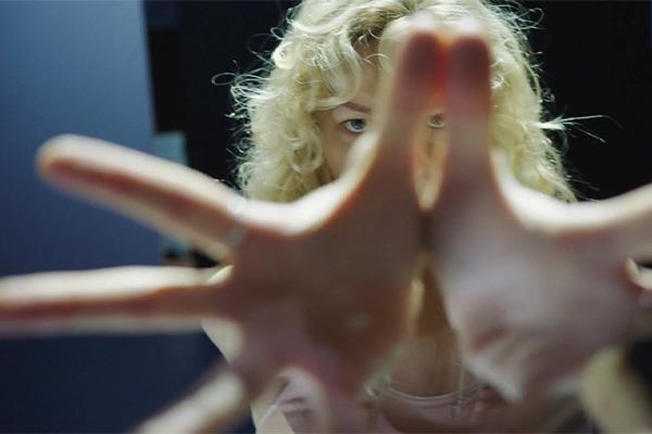 Nainen kädet suoristettuina kameraa kohden