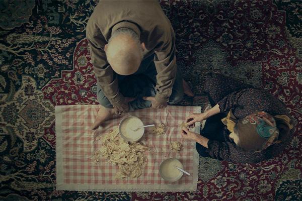 Nainen ja mies syövät maassa istuen