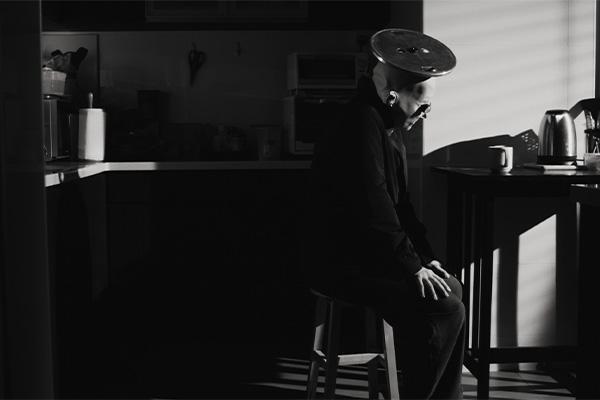 Henkilö istuu keittiössä