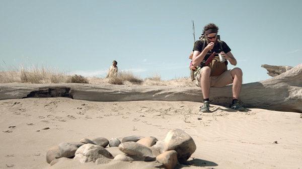 Mies istuu kaatuneella puulla aavikolla / A man sitting on a fallen tree in desert