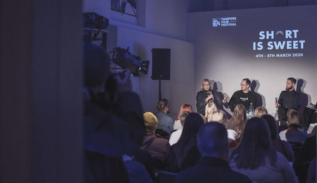 Ihmisiä keskustelemassa lavalla / People talking on a stage